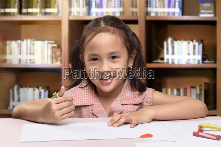smiling asian cute little girl drawing