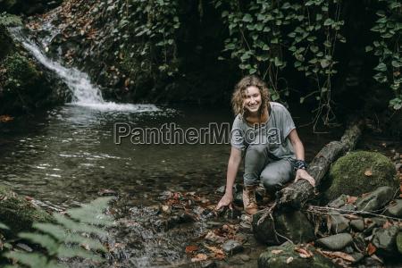 caucasian woman crouching on rock in